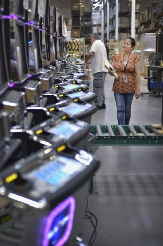 Quality control inspector Edward Guerra, back left, and quality assurance supervisor Gilda Vong make final checks on machines at Konami Gaming in Las Vegas on Friday, Aug. 28, 2015. (Bill Hughes/L ...