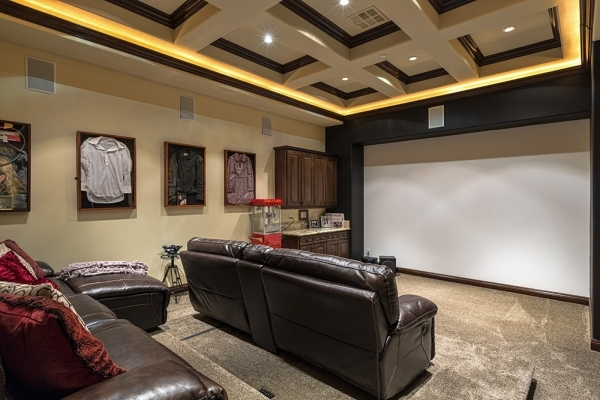 "The home's movie theater has leather recliner seating for seven. Showcased on the walls are shadow boxes holding a Judy Garland-owned blouse, a shirt John Travolta wore in the movie ""Tw ..."