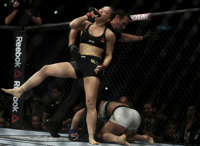 Ronda Rousey (L) of U.S celebrates after defeating Bethe Correia of Brazil during their Ultimate Fighting Championship (UFC) match, a professional mixed martial arts (MMA) competition in Rio de Ja ...