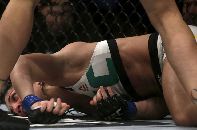 Bethe Correia of Brazil lies on the ground after receiving a punch of Ronda Rousey of U.S during the Ultimate Fighting Championship (UFC) match, a professional mixed martial arts (MMA) competition ...
