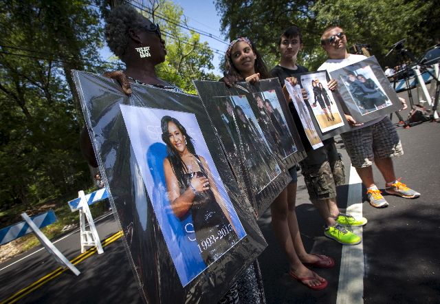 Fans hold pictures of Bobbi Kristina Brown and Whitney Houston as they stand outside the Fairview Cemetery in Westfield, New Jersey, where Bobbi Kristina's burial service is taking place, Au ...