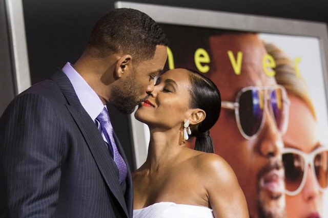 "Cast member Will Smith and his wife Jada Pinkett Smith kiss at the premiere of ""Focus"" at the TCL Chinese theatre in Hollywood, California February 24, 2015. (Mario Anzuoni/Reuters)"