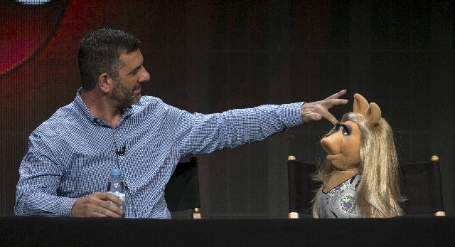"Writer and executive producer Bob Kushell fixes the hair of Muppets character Miss Piggy at a panel for the Disney-ABC television series ""The Muppets"" during the Television Critics Assoc ..."