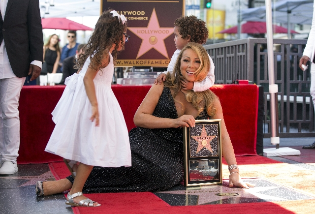 Recording artist Mariah Carey poses on her star with her children Moroccan Scott and Monroe Cannon after it was unveiled on the Hollywood Walk of Fame in Los Angeles, California August 5, 2015. (M ...