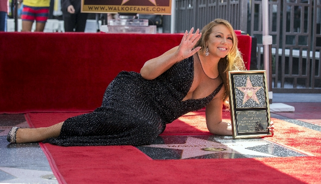 Recording artist Mariah Carey poses on her star after it was unveiled on the Hollywood Walk of Fame in Los Angeles, California August 5, 2015. (Mario Anzuoni/Reuters)
