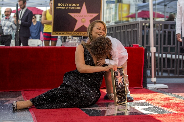 Recording artist Mariah Carey poses on her star with her son Moroccan Scott after it was unveiled on the Hollywood Walk of Fame in Los Angeles, California August 5, 2015.  (Mario Anzuoni/Reuters)