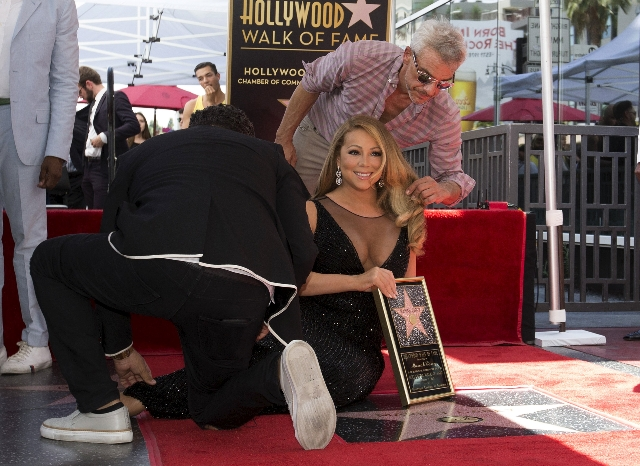 Recording artist Mariah Carey is helped as she poses on her star after it was unveiled on the Hollywood Walk of Fame in Los Angeles, California August 5, 2015. (Mario Anzuoni/Reuters)