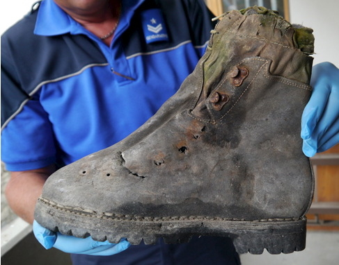 A police officer displays a shoe found in September 2014 near the Matterhorn mountain in Zermatt, Switzerland, in this handout picture released on August 6, 2015 by the Police Cantonale Valaisanne ...