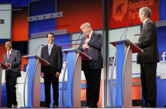 Fellow Republican 2016 U.S. presidential candidates Dr. Ben Carson (L), Wisconsin Governor Scott Walker (2nd L) and former Florida Governor Jeb Bush (R) laugh as fellow candidate and businessman D ...