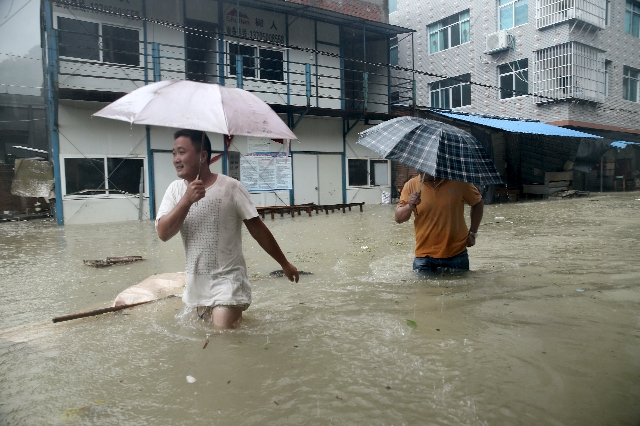 People wade through a flooded street at a town hit by Typhoon Soudelor in Ningde, Fujian province, China, Aug. 9, 2015. (Stringer/Reuters)