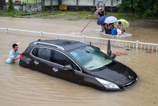 A trapped car is pushed along a flooded street after Typhoon Soudelor hit Fuzhou, Fujian province, China, Aug. 9, 2015. (Stringer/Reuters)