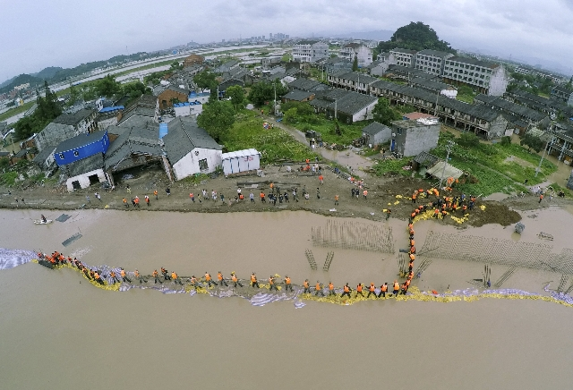 An aerial view shows People's Liberation Army soldiers and local residents placing sand bags to block floodwaters after a dam breached under the influence of Typhoon Soudelor, in Pingyang co ...