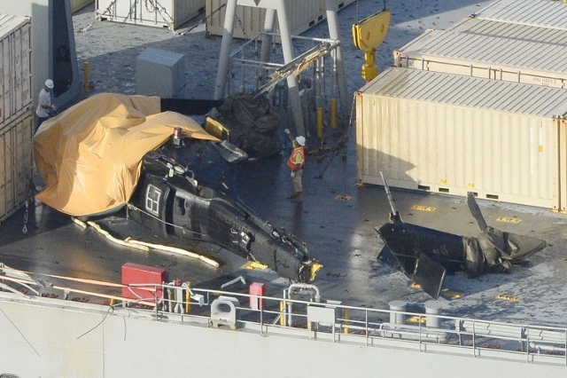 A damaged U.S. Army helicopter rests on the desk of the USNS Red Cloud off Okinawa island, southern Japan, in this photo taken by Kyodo August 12, 2015. (Reuters/Kyodo)