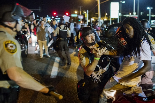 St Louis County police officers hold an anti-police demonstrator in Ferguson, Missouri, August 10, 2015. Police in riot gear clashed with protesters who had gathered in the streets of Ferguson ear ...