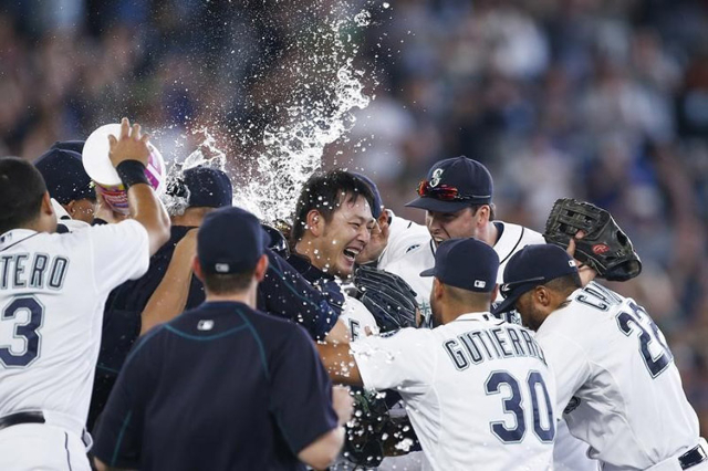 Seattle Mariners pitcher Hisashi Iwakuma (18) celebrates with his teammates following the final out of his no-hit, 3-0 victory against the Baltimore Orioles at Safeco Field. (Joe Nicholson/USA TOD ...