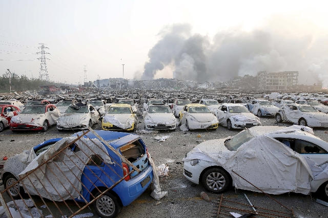 Damaged cars are seen as smoke rises from the debris after the explosions at the Binhai new district in Tianjin, China, August 13, 2015. REUTERS/China Daily