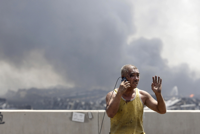 An injured man talks on his mobile phone at the site of the explosions at the Binhai new district in Tianjin August 13, 2015.  REUTERS/Jason Lee