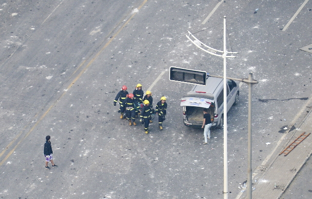 Firefighters carry the body of a victim onto a van after explosions at Binhai new district in Tianjin, China, August 13, 2015.  REUTERS/Stringer