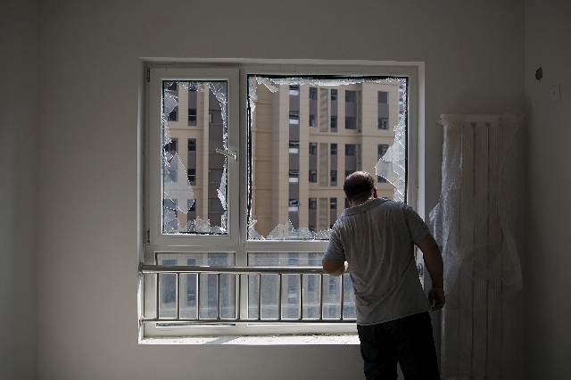 A man looks out from inside a damaged residential building near the site of the explosions at the Binhai new district, Tianjin, August 13, 2015. REUTERS/Damir Sagolj