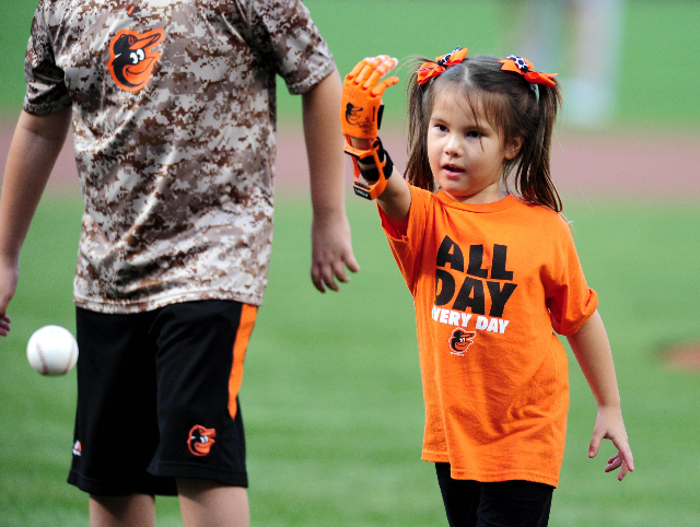 Aug 17, 2015; Baltimore, MD, USA; Hailey Dawson throws out the first pitch with a 3-D printed hand prior to the game between the Oakland Athletics and Baltimore Orioles at Oriole Park at Camden Ya ...