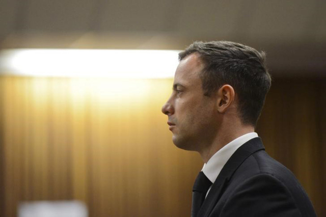 South African Olympic and Paralympic track star Oscar Pistorius stands in the dock as his sentence is delivered at the North Gauteng High Court in Pretoria October 21, 2014. (Herman Verwey/Pool/Re ...