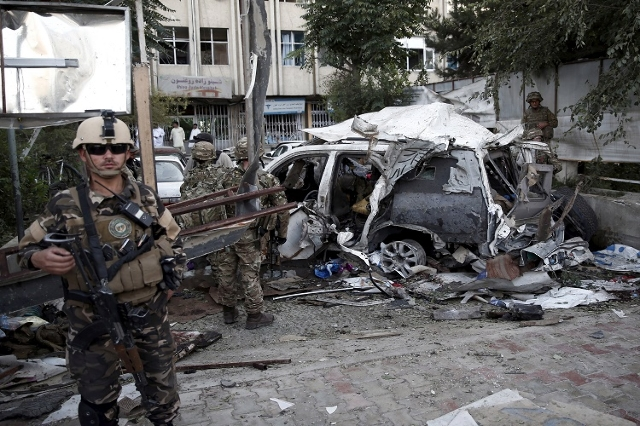 Afghan security personnel (L) keeps watch next to a damaged car belonging to foreigners, after a bomb blast in Kabul, Afghanistan August 22, 2015. (Reuters/Ahmad Masood)