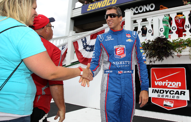 Aug 23, 2015; Long Pond, PA, USA; Verizon IndyCar Series driver Justin Wilson (right) shakes hands with a fan prior to the ABC Supply 500 at Pocono Raceway. (Matthew O'Haren/USA Today Sports)