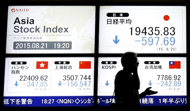 A man walks past an electronic board displaying various Asian countries' stock price index outside a brokerage in Tokyo on Friday. (REUTERS/Issei Kato)