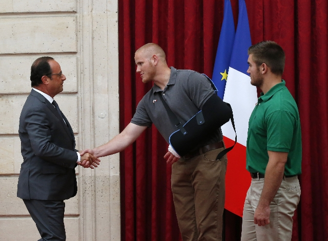 French President Francois Hollande, left, shakes hands with U.S. Airman First Class Spencer Stone as U.S. National Guardsman Alek Skarlatos looks on during a ceremony at the Elysee Palace in Paris ...