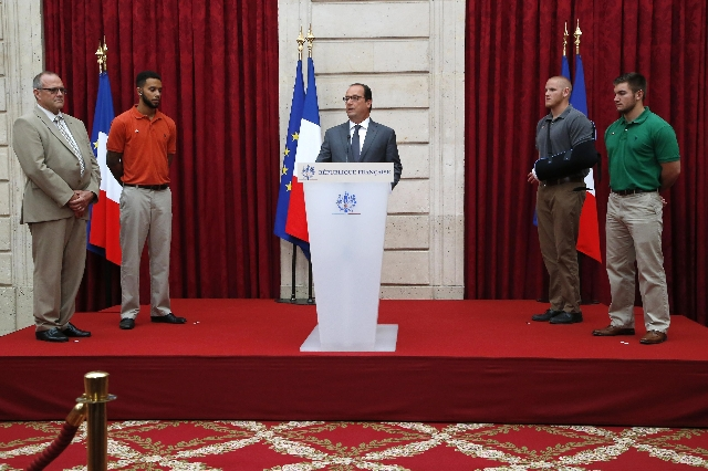 French President Francois Hollande, center, delivers a speech as British businessman Chris Norman, left, U.S. student Anthony Sadler, U.S. Airman First Class Spencer Stone and U.S. National Guards ...