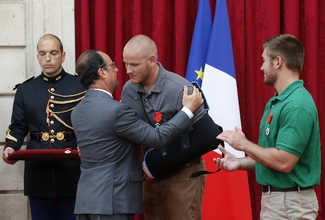 French President Francois Hollande, left, awards U.S. Airman First Class Spencer Stone with the Legion d'Honneur (the Legion of Honour) medal as U.S. National Guardsman Alek Skarlatos applau ...