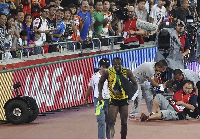 Usain Bolt of Jamaica (front R) limps after being knocked over by a cameraman (R) on a Segway after winning the men's 200 metres final at the 15th IAAF World Championships at the National St ...