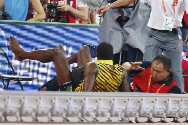 Usain Bolt (L) of Jamaica is knocked over by a cameraman on a Segway after the men's 200m final during the 15th IAAF World Championships at the National Stadium in Beijing, China August 27,  ...
