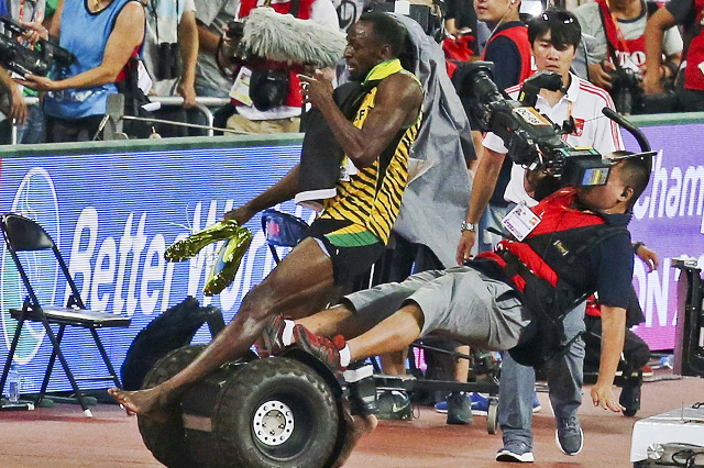 Usain Bolt of Jamaica is hit by a cameraman on a Segway as he celebrates after winning the men's 200 metres final at the 15th IAAF World Championships at the National Stadium in Beijing, Chi ...