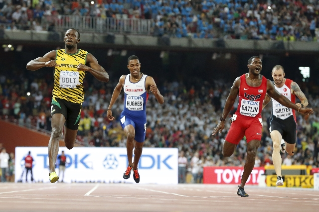 Usain Bolt of Jamaica (L) crosses the finish line ahead of Justin Gatlin (2nd R) from the U.S., Zharnel Hughes of Britain (2nd L) and Ramil Guliyev of Turkey in the men's 200m final during t ...
