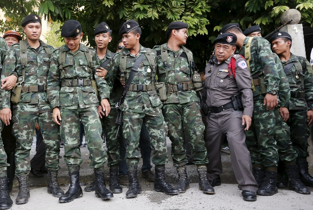 A Thai Royal Police officer walks past Thai army soldiers at the site where a suspect of the recent Bangkok blast was arrested, in Bangkok August 29, 2015. Police hunting for the perpetrators of T ...