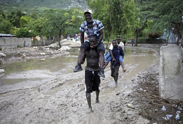 Men carry others, so they do not soil their shoes and clothes, through a mudslide caused by Tropical Storm Erika in Carries, Haiti, on Saturday. (REUTERS/Andres Martinez Casares)