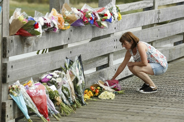 A woman lays flowers near to the site where a Hawker Hunter fighter jet crashed onto the A27 road at Shoreham near Brighton, Britain August 23, 2015. A jet aircraft ploughed into several cars on a ...
