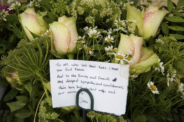 A message is seen on a floral tribute left near the site where a Hawker Hunter fighter jet crashed onto the A27 road at Shoreham near Brighton, Britain August 23, 2015. A jet aircraft ploughed int ...