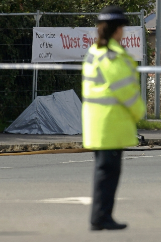 A police officer stands guard in front of a forensic tent at the site where a Hawker Hunter fighter jet crashed onto the A27 road at Shoreham near Brighton, Britain August 23, 2015. A jet aircraft ...