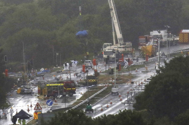 A crane lifts an object under a blue tarpaulin as emergency services and crash investigation officers continue to work at the site where a Hawker Hunter fighter jet crashed onto the A27 road at Sh ...