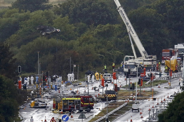 A crane removes the remains of a Hawker Hunter fighter jet that crashed onto the A27 road at Shoreham near Brighton, Britain August 24, 2015. The death toll after a jet plane ploughed into a busy  ...