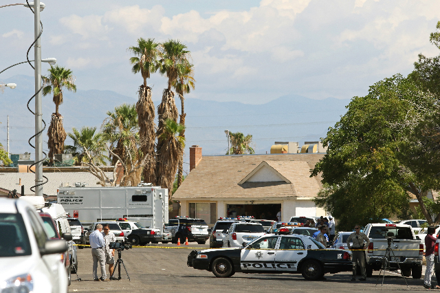 Police respond to an officer-involved shooting at the 6900 block of Berkshire Place Friday, Aug. 7, 2015, in Las Vegas. Police were called to a home where shots were fired. A suspect was taken by  ...