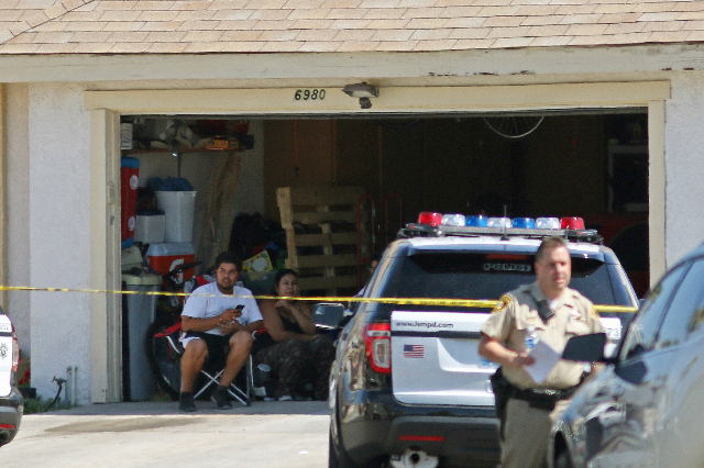 People sit in a garage at a home located on the 6900 block of Berkshire Place Friday, Aug. 7, 2015, in Las Vegas. Police were called to a home on Berkshire Place where shots were fired. A suspect  ...