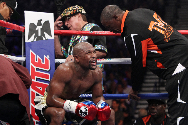 Floyd Mayweather Jr. talks to his trainer, Floyd Mayweather Sr., in between rounds of his welterweight unification boxing match against Manny Pacquiao at the MGM Grand Garden Arena in Las Vegas on ...