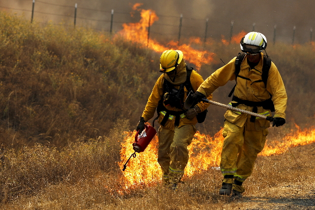 A Cal Fire firefighter sets a backfire with a driptorch along Highway 20 during the Rocky Fire near Lower Lake, California, Aug. 3, 2015. (Stephen Lam/Reuters)