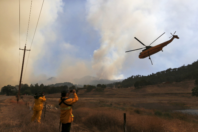 A firefighting helicopter hovers along Highway 20 during the Rocky Fire near Lower Lake, California, Aug. 3, 2015. (Stephen Lam/Reuters)