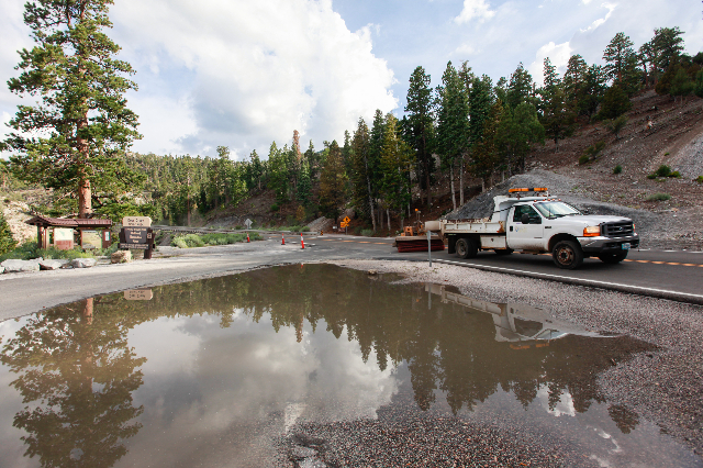 A Nevada Department of Transportation vehicles passes by as clean up goes on along State Route 158 following a flash flood in the Spring Mountains National Recreation Area on Friday, July 31, 2015 ...