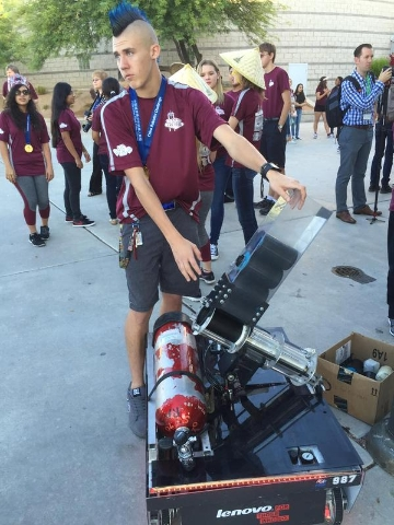 Spartan Brendan Mulcahy shows off T-shirt cannon that the Cimarron-Memorial High School robotics team built using old parts. (Neal Morton/Las Vegas Review-Journal)