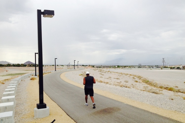 As storm drop rain on the Sheep Mountains to the north, Ronald (who would not give his last name) walks along the path next to the Angel Park Detemtion Basin in Las Vegas on Saturday, Aug. 1. 2015 ...
